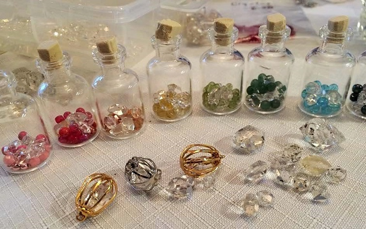 Small vials with Herkimer diamonds, various color beads and Swarovski crystals.   (Plus some Herkimer diamonds in cages on table to be hung on necklace cord). Art Rains
